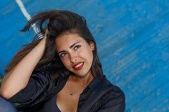 年轻人晒黑了一件短的上面和衬衣的摆在对蓝色木墙壁的妇女有美好的现代构成的和头发 免版税库存图片