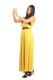 年轻人晒黑了在拍与手机的黄色礼服的秀丽照片 免版税库存图片