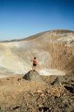 年轻人晒黑了摆在火山火山口前面的男性模型 库存图片
