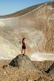 年轻人晒黑了摆在火山火山口前面的男性模型 免版税图库摄影