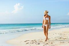 年轻人晒黑了比基尼泳装的妇女在热带自然海滩 免版税库存照片