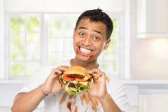 年轻人有一个巨大欲望吃汉堡 免版税库存照片