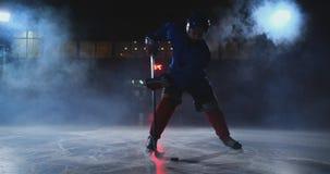 人有一个顽童的曲棍球运动员在冰竞技场显示滴下的移动直接地向照相机和看直接入 股票视频