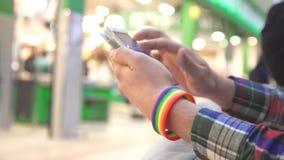 人有一个LGBT镯子的` s手使用一个手机 股票录像