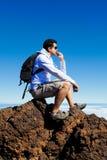 年轻人有休息在云彩的一座高山在Teide Moun 图库摄影