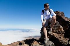 年轻人有休息在云彩的一座高山 库存图片
