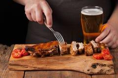 人有叉子立即可食的猪排的厨师串,说谎在一张老木桌上 一个人尝试对低度黄啤酒快餐和饮料  免版税库存照片