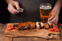 人有叉子立即可食的猪排的厨师串,说谎在一张老木桌上 一个人尝试对低度黄啤酒快餐和饮料  免版税库存图片