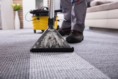 人有吸尘器的清洁地毯 免版税库存照片