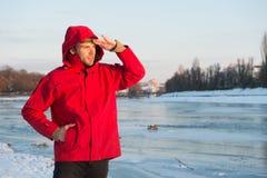 人有敞篷的穿戴夹克在冷淡的冬日 人有胡子的立场温暖的夹克多雪的自然背景 抗性风 免版税库存照片