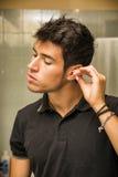 年轻人有棉花棒的清洁耳朵 免版税库存照片