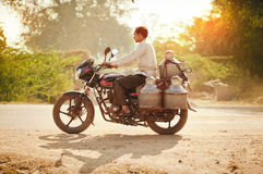 人有牛奶罐头的骑马摩托车 免版税库存图片