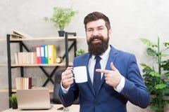 人有胡子的商人举行咖啡杯立场办公室背景 成功的人民喝咖啡 饮用的咖啡 库存图片