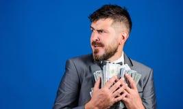 人有胡子的商人举行堆金钱蓝色背景 惊奇的商人感觉象有全部的窃贼现金 免版税库存照片