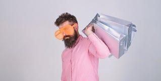 人有胡子的行家穿戴太阳镜拿着束购物带来 在黑星期五,购物 与束纸的愉快的购物 免版税图库摄影