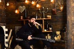 人有胡子的音乐家喜欢与低音吉他,木背景 舒适温暖的大气戏剧松弛灵魂的人 免版税库存图片