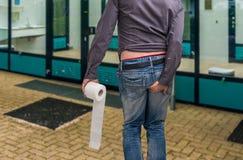 人有腹泻 举行卫生纸和他的人靶垛 免版税库存图片