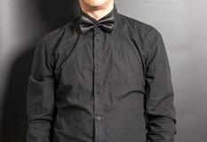 人有黑弓的穿戴的黑衬衣 免版税库存照片