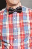 人有黑蝶形领结的穿戴的方格的衬衣在灰色 库存图片