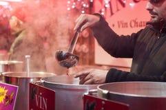 人服务特写镜头仔细考虑了酒在圣诞节市场上 免版税库存照片