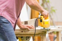 年轻人木匠与电竖锯一起使用 图库摄影