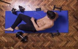 年轻人松弛智能手机举起了看法锻炼席子 免版税库存照片