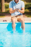 人松弛游泳池边 库存图片