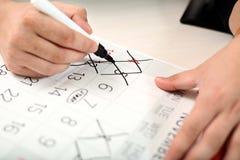 人标记在日历的几天与标志 免版税库存图片