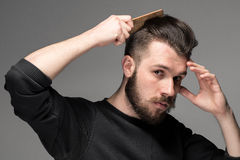 年轻人梳子他的头发 免版税库存图片