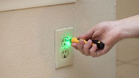 人检查是否有在壁上插座的力量有工具的 库存图片