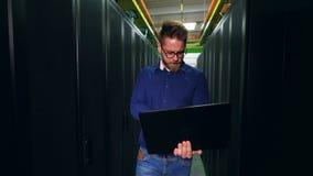 人检查机架与计算机在数据中心,与膝上型计算机一起使用 工作在现代数据的服务器技术员 股票录像