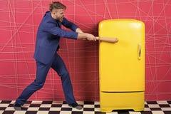 人正式典雅的衣服打了与木棒减速火箭的葡萄酒黄色冰箱 饥饿的学士要在冰箱附近吃 免版税库存照片