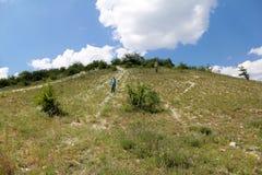 年轻人步行沿着向下在石路的小山 免版税库存照片