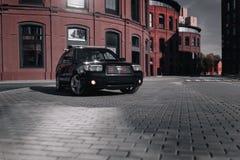 黑人汽车Subaru林务员停放了靠近现代红色大厦在莫斯科在白天 免版税库存图片