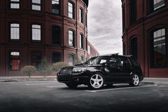 黑人汽车Subaru林务员停放了靠近现代红色大厦在莫斯科在白天 免版税库存照片