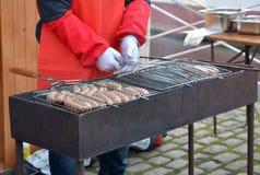 人油煎在街道火盆的香肠 免版税库存照片