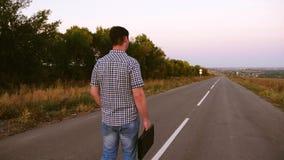 人沿有一个黑公文包的一条柏油路走在他的手上 免版税图库摄影