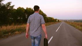 人沿有一个黑公文包的一条柏油路走在他的手上 免版税库存图片