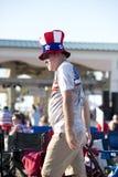 人沿穿爱国帽子和衬衣的海滩木板走道走 库存照片