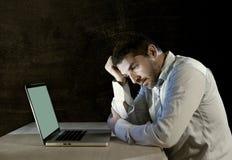 年轻人注重了工作在有计算机膝上型计算机的书桌上的商人在失望和消沉 免版税图库摄影