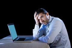 年轻人注重了工作在有计算机膝上型计算机的书桌上的商人在失望和消沉 图库摄影