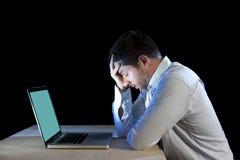 年轻人注重了工作在有计算机膝上型计算机的书桌上的商人在失望和消沉 免版税库存图片