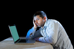 年轻人注重了工作在有计算机膝上型计算机的书桌上的商人在失望和消沉 库存图片