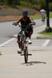 年轻人流行在自行车的一个自行车前轮离地平衡特技并且乘坐它 库存照片