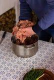 人混合在金属平底锅的很多绞细牛肉 免版税库存照片