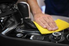 人清洁汽车与旧布的变速杆, 图库摄影