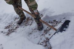 人清除围场与铁锹的雪 美好的大量横向降雪冬天 高级雪 斯诺伊随风飘飞的雪 免版税图库摄影