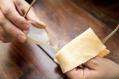 人清洗眼睛玻璃与microfibre布料, hornrims 免版税库存照片