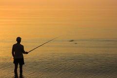 人渔在日出的海 免版税库存照片