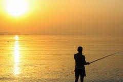 人渔在日出的海 免版税图库摄影